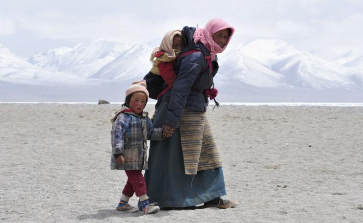 A Tibetan woman carries her daughter on her back as she holds her son's hands near Lake Namtso. A new study finds that glacial melting in Tibet has created many more lakes in the region. Reuters