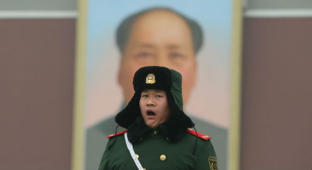 A policeman stands guard in front of a giant portrait of the late chairman Mao Zedong at the Tiananmen Square in 2013 in Beijing, China. (Feng Li/Getty Images)